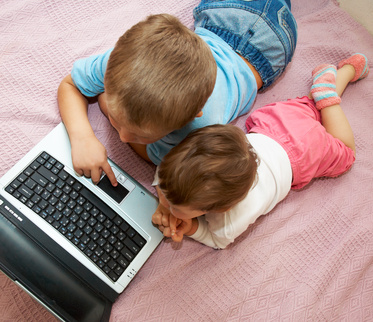 Little girl and boy lying in front of laptop